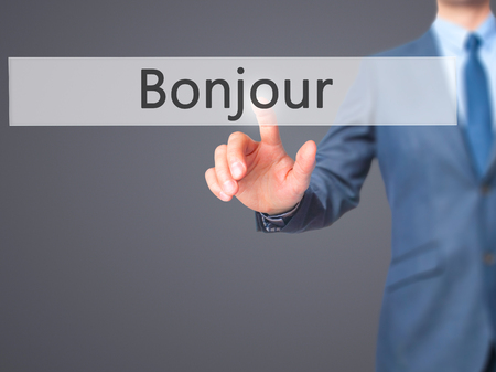 bonjour: Bonjour (Good Morning in French) - Businessman hand touch  button on virtual  screen interface. Business, technology concept. Stock Photo