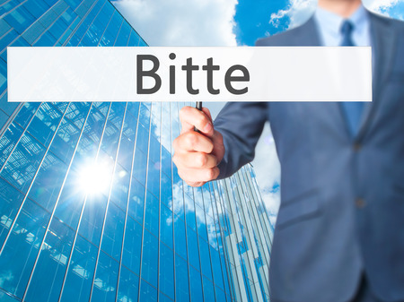 Bitte (Please in German) - Businessman hand holding sign. Business, technology, internet concept. Stock Photo