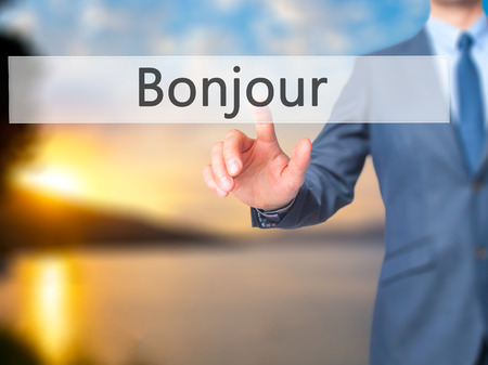 Bonjour (Good Morning in French) - Businessman hand touch  button on virtual  screen interface. Business, technology concept. Stock Photo