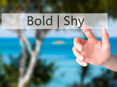 bashful: Bold Shy - Hand pressing a button on blurred background concept . Business, technology, internet concept. Stock Photo