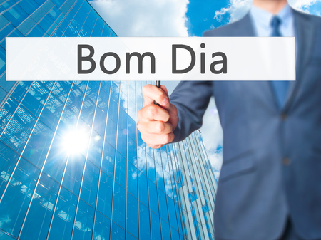 Bom Dia (In portuguese - Good Morning) - Businessman hand holding sign. Business, technology, internet concept. Stock Photo