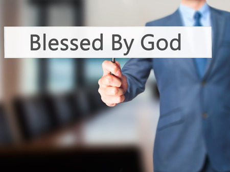 preachment: Blessed By God - Businessman hand holding sign. Business, technology, internet concept. Stock Photo Stock Photo