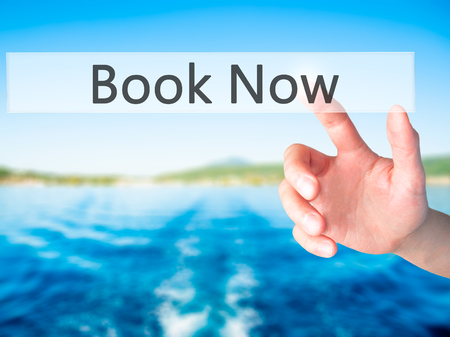 reserve: Book Now - Hand pressing a button on blurred background concept . Business, technology, internet concept. Stock Photo