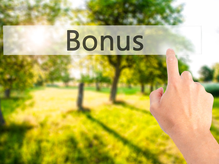 Bonus - Hand pressing a button on blurred background concept . Business, technology, internet concept. Stock Photo Stock Photo