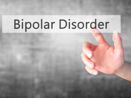 psychosocial: Bipolar Disorder - Hand pressing a button on blurred background concept . Business, technology, internet concept. Stock Photo
