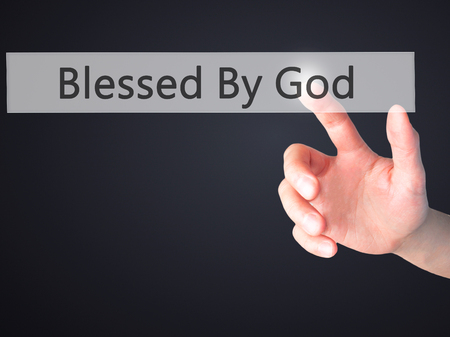 god button: Blessed By God - Hand pressing a button on blurred background concept . Business, technology, internet concept. Stock Photo