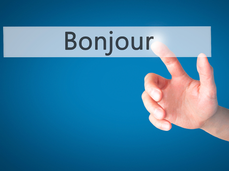 bonjour: Bonjour (Good Morning in French) - Hand pressing a button on blurred background concept . Business, technology, internet concept. Stock Photo Stock Photo