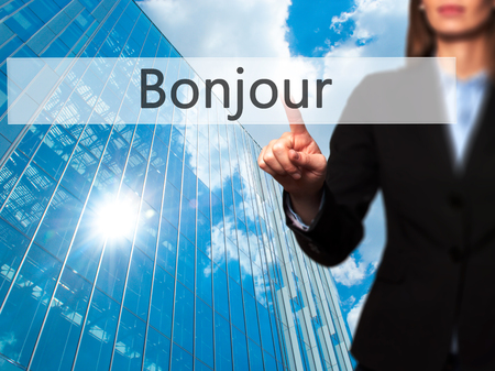 bonjour: Bonjour (Good Morning in French) - Young girl working with virtual screen an touching button. Technology, internet concept. Stock Photo
