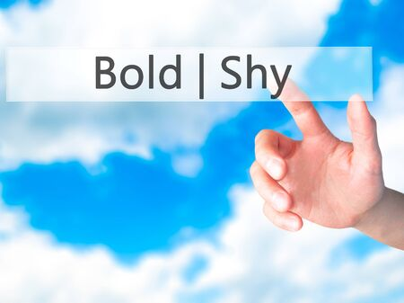 bold: Bold Shy - Hand pressing a button on blurred background concept . Business, technology, internet concept. Stock Photo