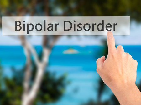 depressive: Bipolar Disorder - Hand pressing a button on blurred background concept . Business, technology, internet concept. Stock Photo