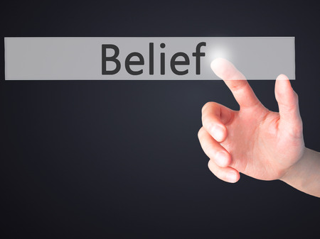 beliefs: Belief - Hand pressing a button on blurred background concept . Business, technology, internet concept. Stock Photo