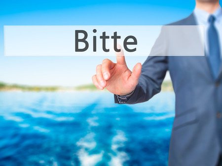 cordiality: Bitte (Please in German) - Businessman hand touch  button on virtual  screen interface. Business, technology concept. Stock Photo