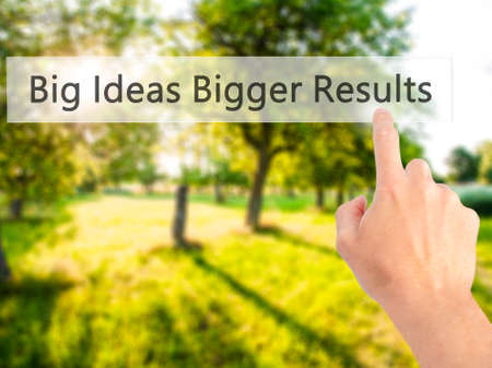 Big Ideas Bigger Results - Hand pressing a button on blurred background concept . Business, technology, internet concept. Stock Photo