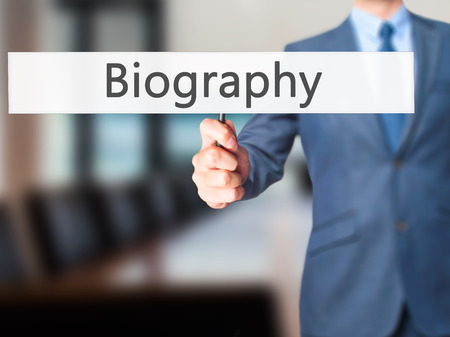 unveil: Biography - Businessman hand holding sign. Business, technology, internet concept. Stock Photo