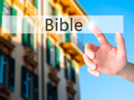 christian trust: Bible - Hand pressing a button on blurred background concept . Business, technology, internet concept. Stock Photo Stock Photo