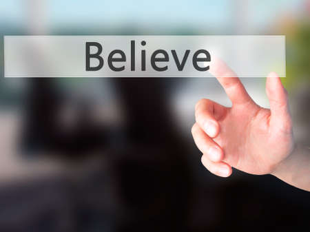 Believe - Hand pressing a button on blurred background concept . Business, technology, internet concept. Stock Photo