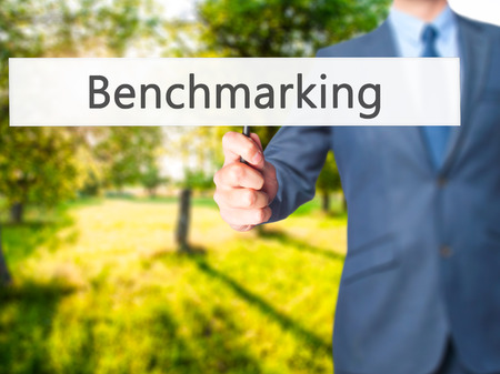 Benchmarking - Businessman hand holding sign. Business, technology, internet concept. Stock Photo
