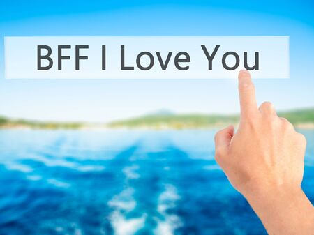 postit note: BFF I Love You - Hand pressing a button on blurred background concept . Business, technology, internet concept. Stock Photo