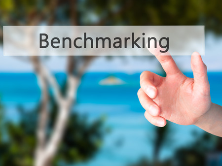 proven: Benchmarking - Hand pressing a button on blurred background concept . Business, technology, internet concept. Stock Photo
