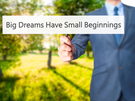 Big Dreams Have Small Beginnings - Businessman hand holding sign. Business, technology, internet concept. Stock Photo