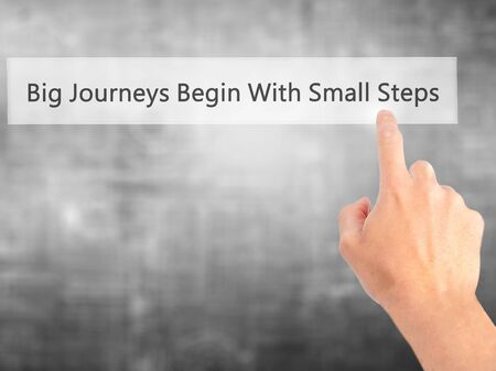 daunting: Big Journeys Begin With Small Steps - Hand pressing a button on blurred background concept . Business, technology, internet concept. Stock Photo Stock Photo