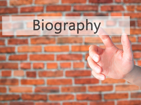 Biography - Hand pressing a button on blurred background concept . Business, technology, internet concept. Stock Photo