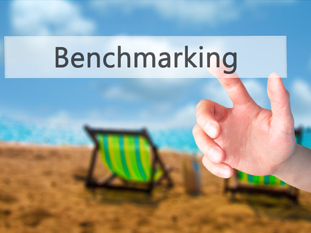 operational: Benchmarking - Hand pressing a button on blurred background concept . Business, technology, internet concept. Stock Photo