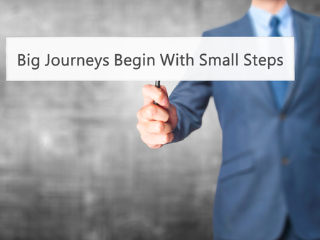 daunting: Big Journeys Begin With Small Steps - Businessman hand holding sign. Business, technology, internet concept. Stock Photo