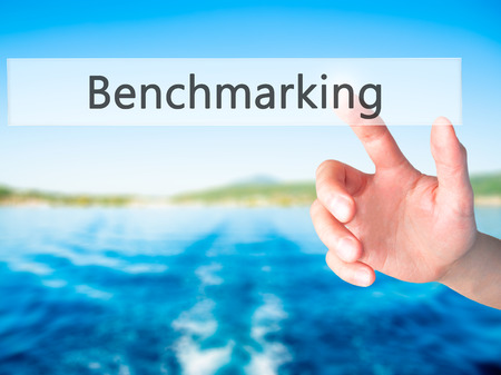 benchmarking: Benchmarking - Hand pressing a button on blurred background concept . Business, technology, internet concept. Stock Photo
