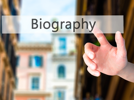 biography: Biography - Hand pressing a button on blurred background concept . Business, technology, internet concept. Stock Photo