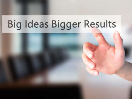 bigger: Big Ideas Bigger Results - Hand pressing a button on blurred background concept . Business, technology, internet concept. Stock Photo