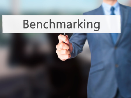 benchmarking: Benchmarking - Businessman hand holding sign. Business, technology, internet concept. Stock Photo