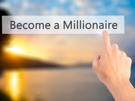 millionaire: Become a Millionaire - Hand pressing a button on blurred background concept . Business, technology, internet concept. Stock Photo