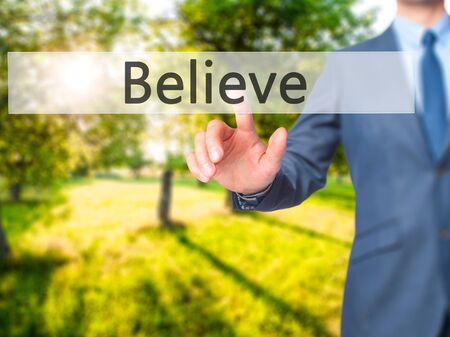 challenges ahead: Believe - Businessman hand pushing button on touch screen. Business, technology, internet concept. Stock Image