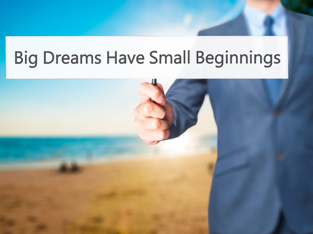 beginnings: Big Dreams Have Small Beginnings - Businessman hand holding sign. Business, technology, internet concept. Stock Photo