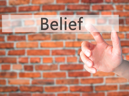 guidepost: Belief - Hand pressing a button on blurred background concept . Business, technology, internet concept. Stock Photo