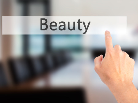 personality development: Beauty - Hand pressing a button on blurred background concept . Business, technology, internet concept. Stock Photo