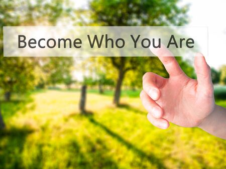 Become Who You Are - Hand pressing a button on blurred background concept . Business, technology, internet concept. Stock Photo