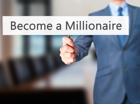 hombre millonario: Become a Millionaire - Businessman hand holding sign. Business, technology, internet concept. Stock Photo