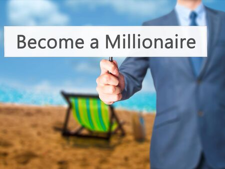 become: Become a Millionaire - Businessman hand holding sign. Business, technology, internet concept. Stock Photo
