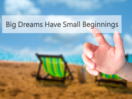 Big Dreams Have Small Beginnings - Hand pressing a button on blurred background concept . Business, technology, internet concept. Stock Photo