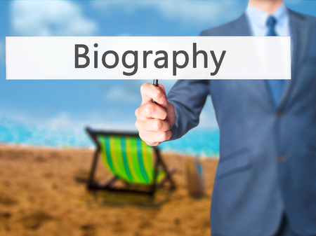 biography: Biography - Businessman hand holding sign. Business, technology, internet concept. Stock Photo