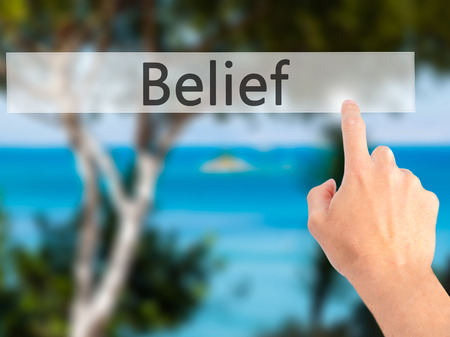 posit: Belief - Hand pressing a button on blurred background concept . Business, technology, internet concept. Stock Photo