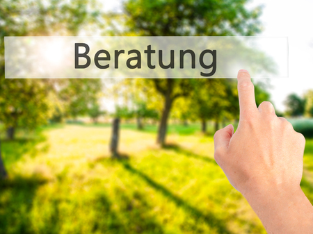 Beratung (Advice in German) - Hand pressing a button on blurred background concept . Business, technology, internet concept. Stock Photo Stock Photo
