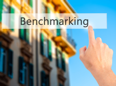 Benchmarking - Hand pressing a button on blurred background concept . Business, technology, internet concept. Stock Photo