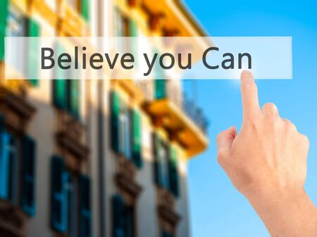 Believe you Can - Hand pressing a button on blurred background concept . Business, technology, internet concept. Stock Photo