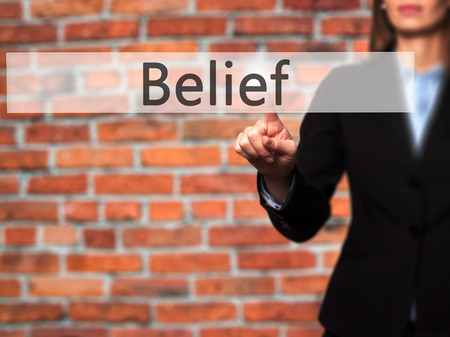 Belief -  Successful businesswoman making use of innovative technologies and finger pressing button. Business, future and technology concept. Stock Photo