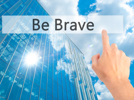 Be Brave - Hand pressing a button on blurred background concept . Business, technology, internet concept. Stock Photo Stock Photo