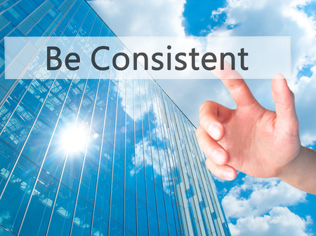 constant: Be Consistent - Hand pressing a button on blurred background concept . Business, technology, internet concept. Stock Photo Stock Photo