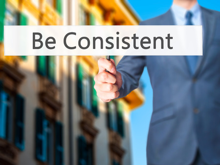 persist: Be Consistent - Business man showing sign. Business, technology, internet concept. Stock Photo Stock Photo